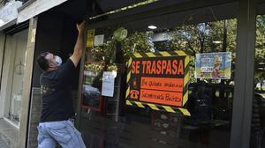 Un hombre baja la persiana de su negocio, en traspaso por la caída de ingresos a raíz del coronavirus, este jueves 16 de julio en València.