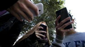 Jóvenes utilizando teléfonos móviles.