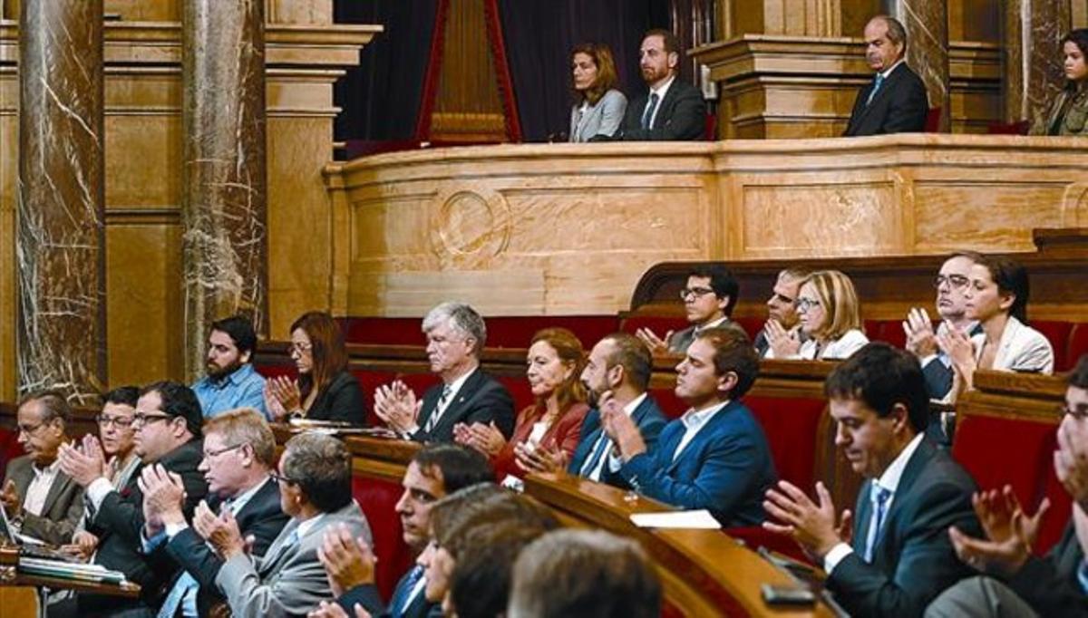 Los diputados aplauden tras la lectura de la declaración institucional en el Parlament, ayer.