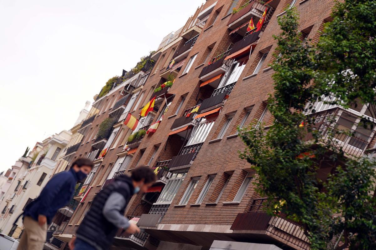 Dos vecinos pasan bajo un edificio decorado con banderas de España en la calle Núñez de Balboa, del distrito madrileño de Salamanca.
