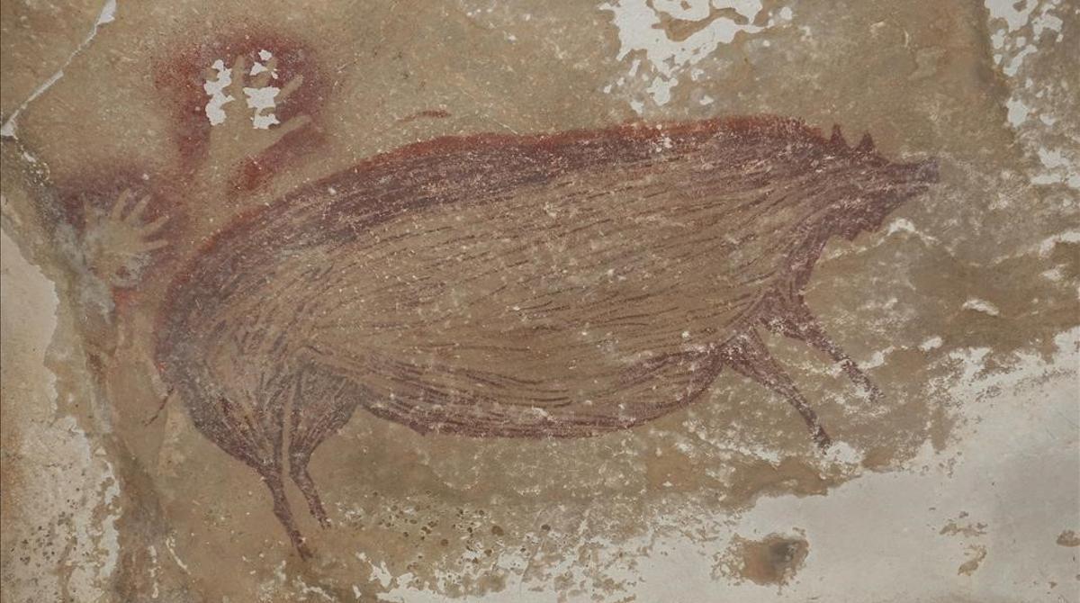 Descubren en Indonesia la pintura rupestre figurativa más antigua del mundo. En la foto, detalle de una de las pinturas rupestres halladas en la Isla de Célebes (Indonesia) en el que se ve un jabalí verrugoso junto a la estampa de dos manos