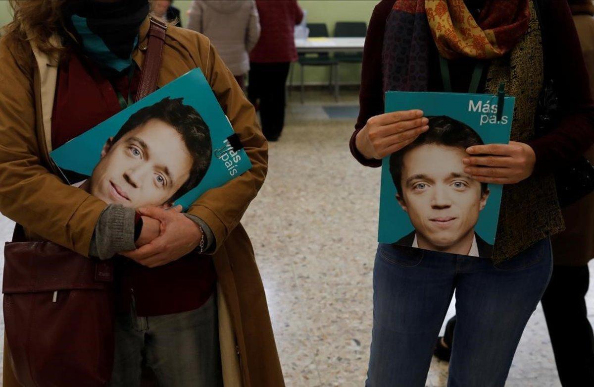 Dos personas con imágenes de Íñigo Errejón, en un colegio electoral en Madrid.
