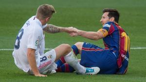 Kroos y Messi se ayudan mutuamente a incorporarse tras un choque.