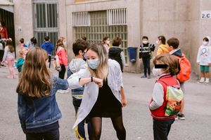 Profesora saludando con el codo a los alumnos.