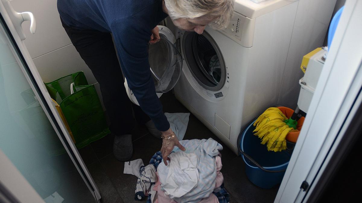 Una mujer pone la lavadora en su casa.