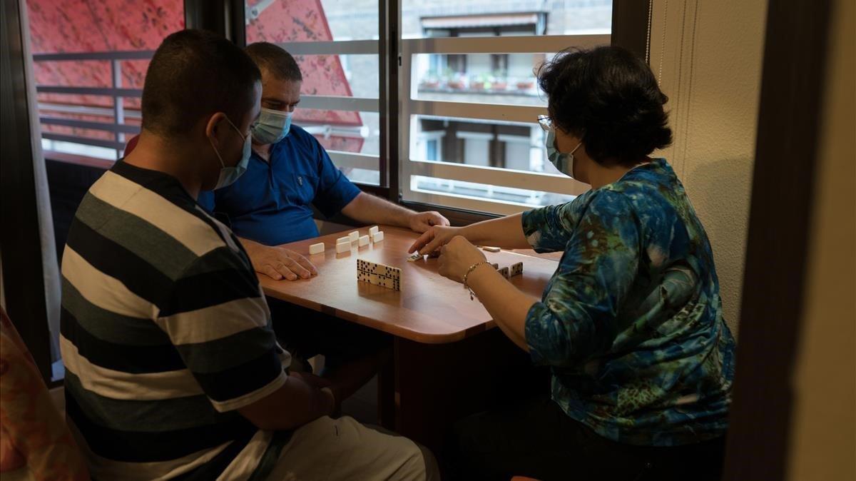 Álex Moreno (con camiseta a rayas) juega al dominó con sus padres en su domicilio, el pasado agosto.