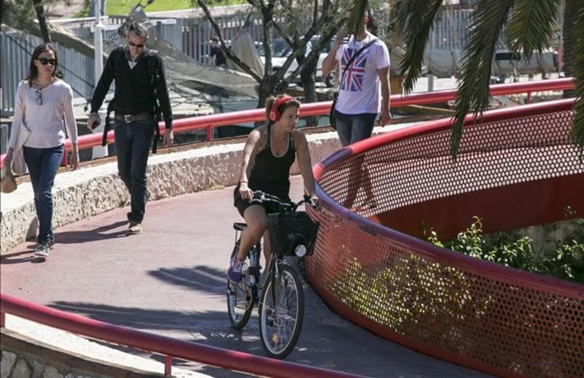 Una ciclista con auriculares circula por las pasarelas del Moll de la Fusta.