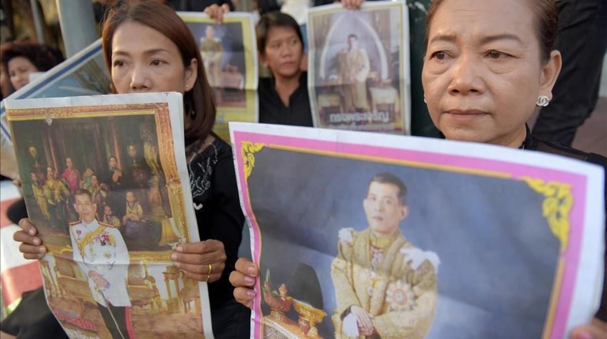 Mujeres sostienen imágenes del príncipe tailandés Maha Vajiralongkom, en el exterior del Gran Palacio, en Bangkok, antes de la proclamación, este jueves.