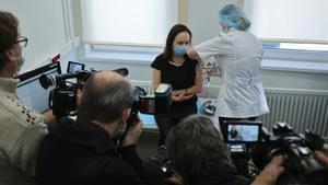 Unos periodistas presentes cuando una mujer recibe un pinchazo mientras le inyectan la vacuna Sputnik V.