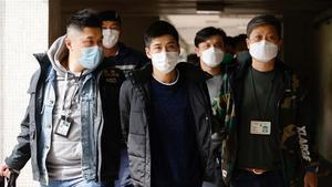 El activista Lester Shum, rodeado de policías durante su detención este lunes en Hong Kong.
