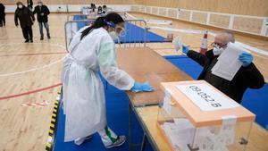 Una mujer desinfecta una mesa electoral en un colegio de Barcelona.