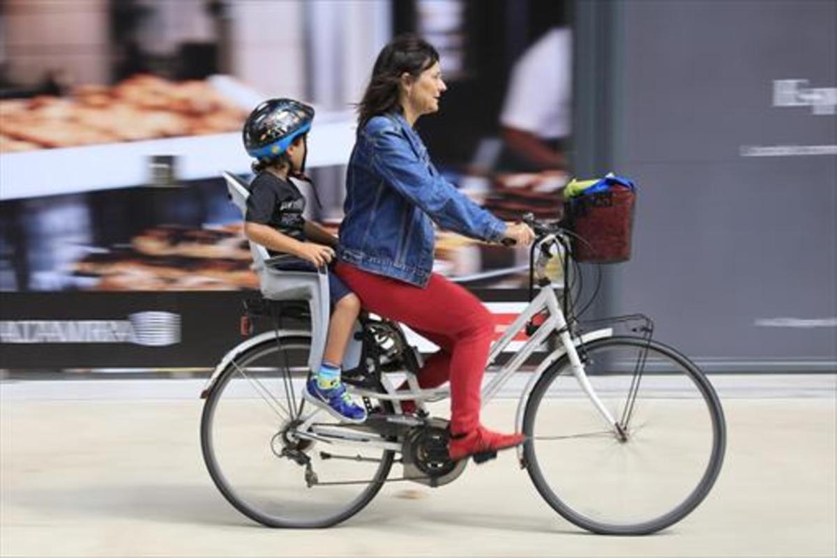 Una madre lleva a su hijo en bicicleta en el Poblenou.
