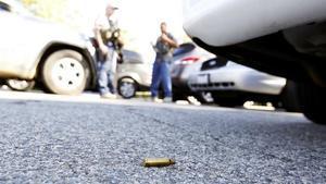 Un casquillo de bala en el suelo utilizado en el tiroteo,mientras la policía asegura el área.