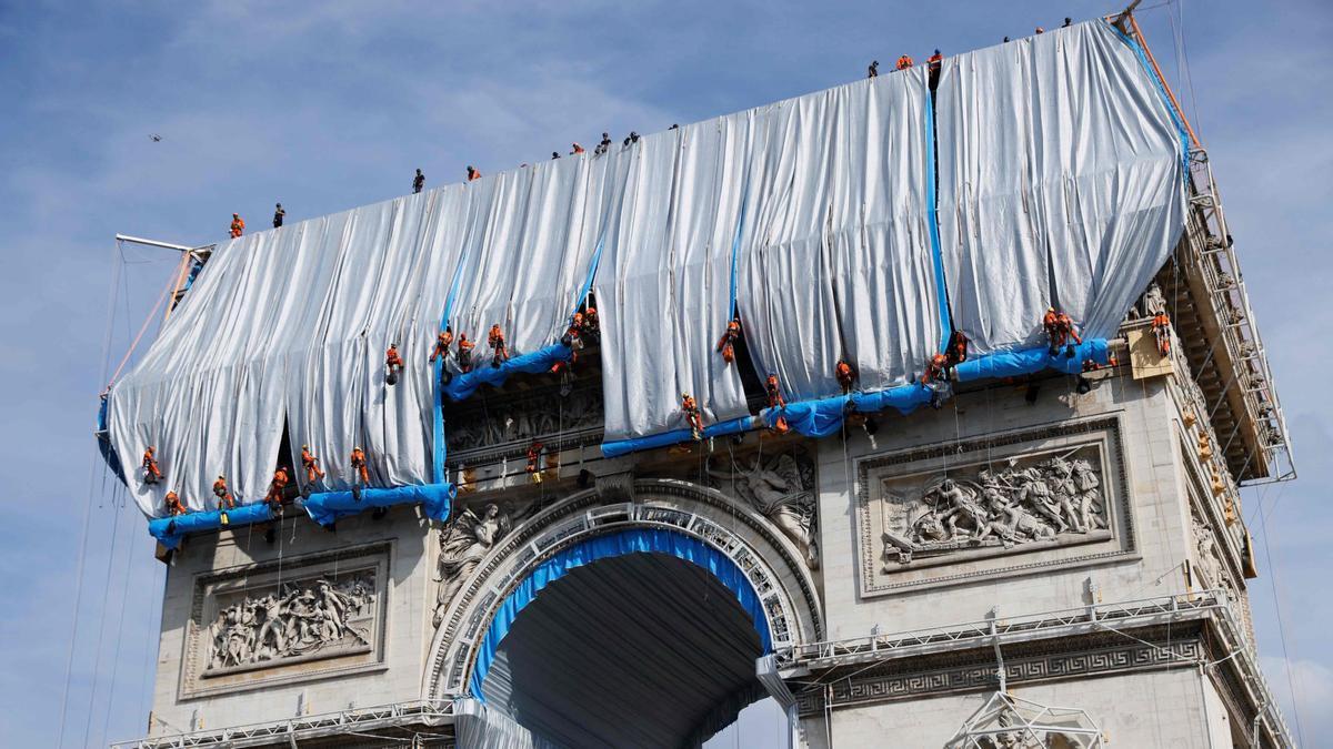 Obreros envuelven el Arco de Triunfo de París.