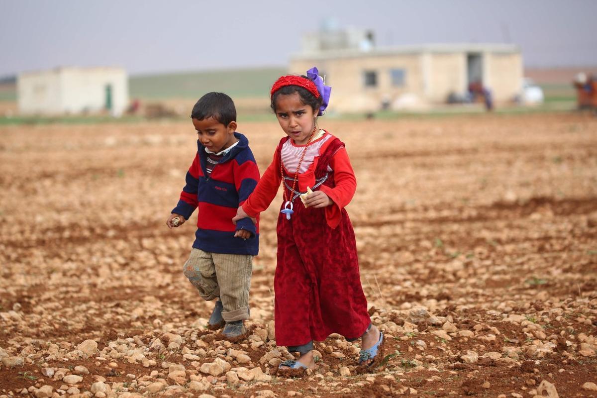 Dos niños se pasean por el campamento para desplazados en Jarufiya.
