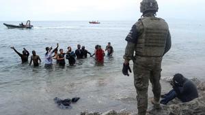 Un legionario español, frente a ciudadanos marroquís que intentaron entrar a nado a España cruzando la frontera en Ceuta.