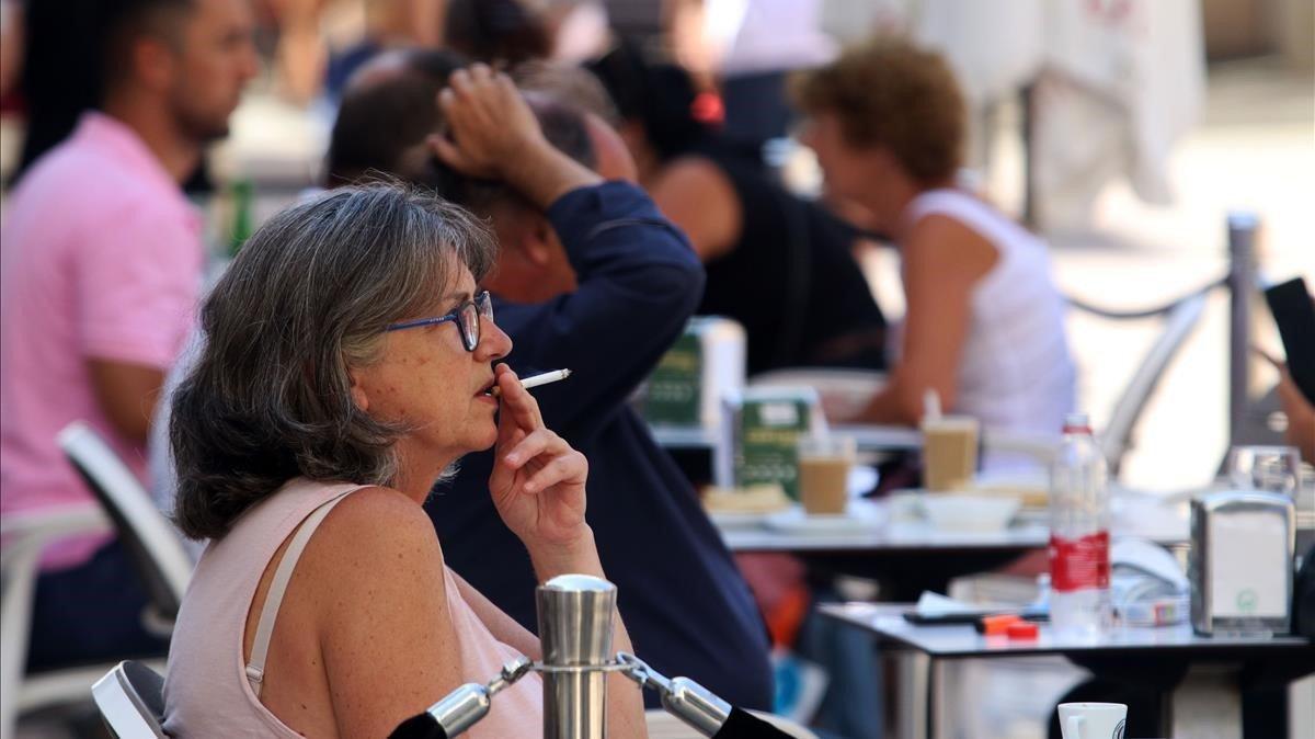 Una mujer fumando en una terraza.