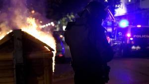 Un policía antidisturbios, junto a un contenedor de basura incenciado en Burgos.