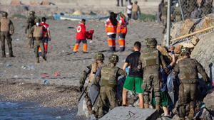 Miembros del ejército ayudan a varios inmigrantes a su llegada a la playa de El Tarajal, junto a la valla fronteriza , enCeutaeste miércoles.