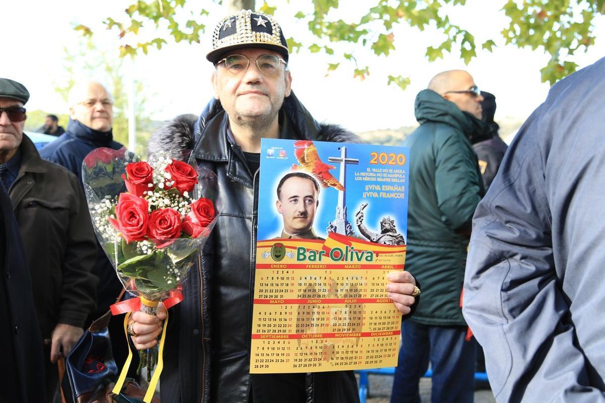 Un adepto con unas flores y enseñando el 'merchandising' de la simbología franquista.