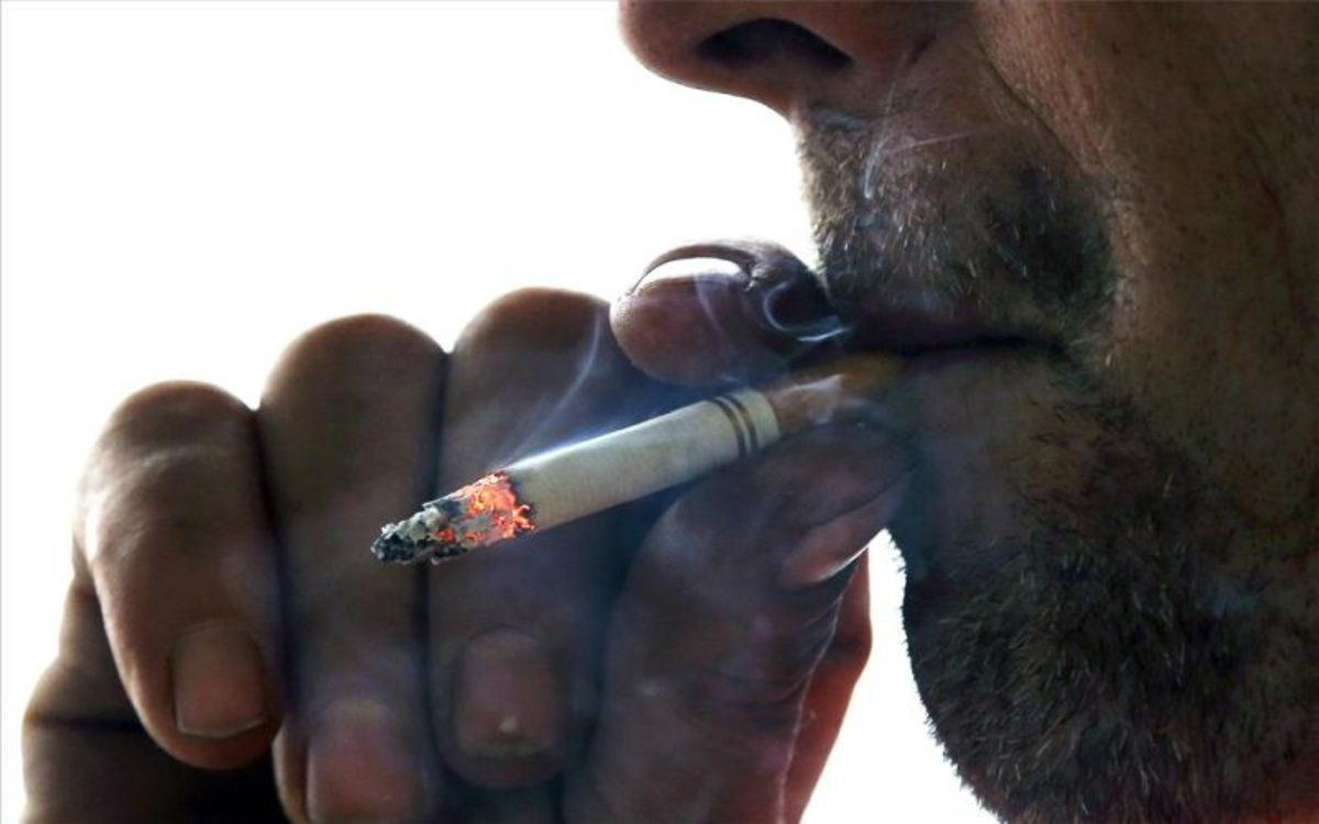 Un hombre fuma un cigarrillo.
