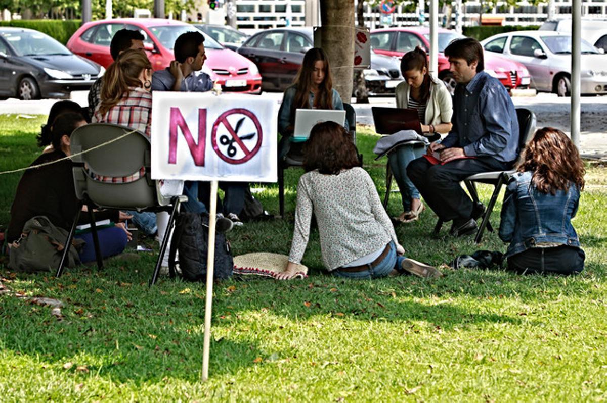 Un grupo de estudiantes da clase al aire libre junto a una camparta contra los recortes en educación