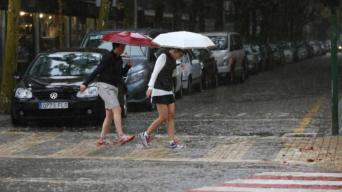 Unas mujeres cruzan la calle en un día de lluvia en Salou.