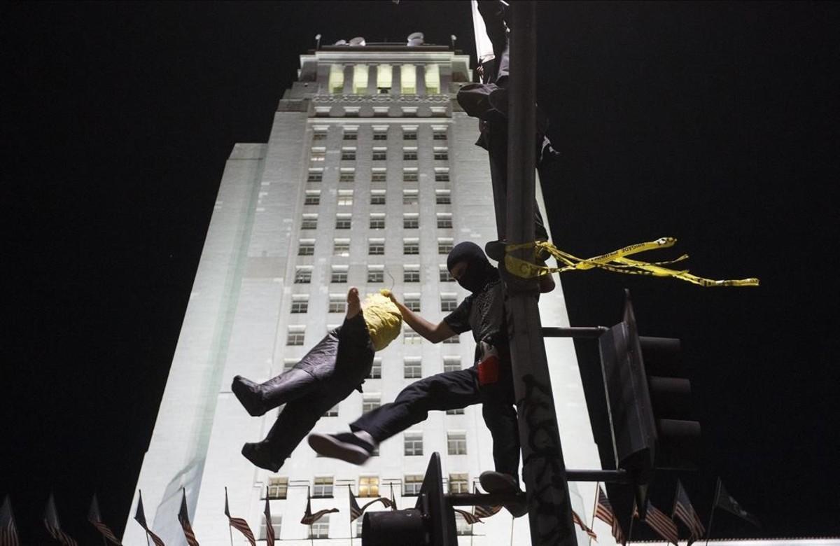Un manifestante golpea una piñataque representa a Donald Trump.