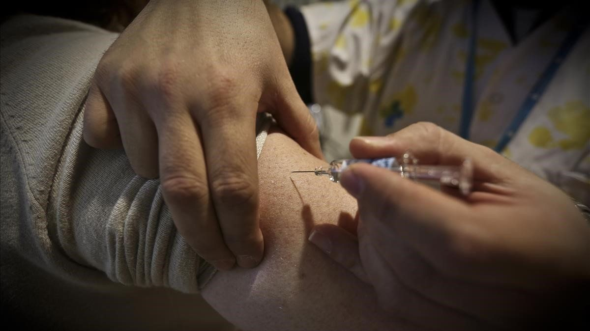 Una enfermera pone una vacuna a un paciente, en una foto de archivo.