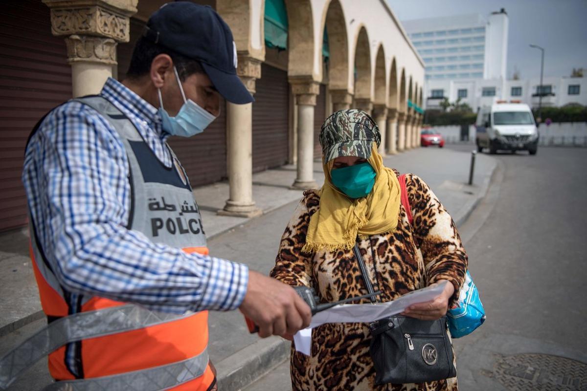 Un vigilantepide la documentación a una mujer en Casablanca, Marruecos.