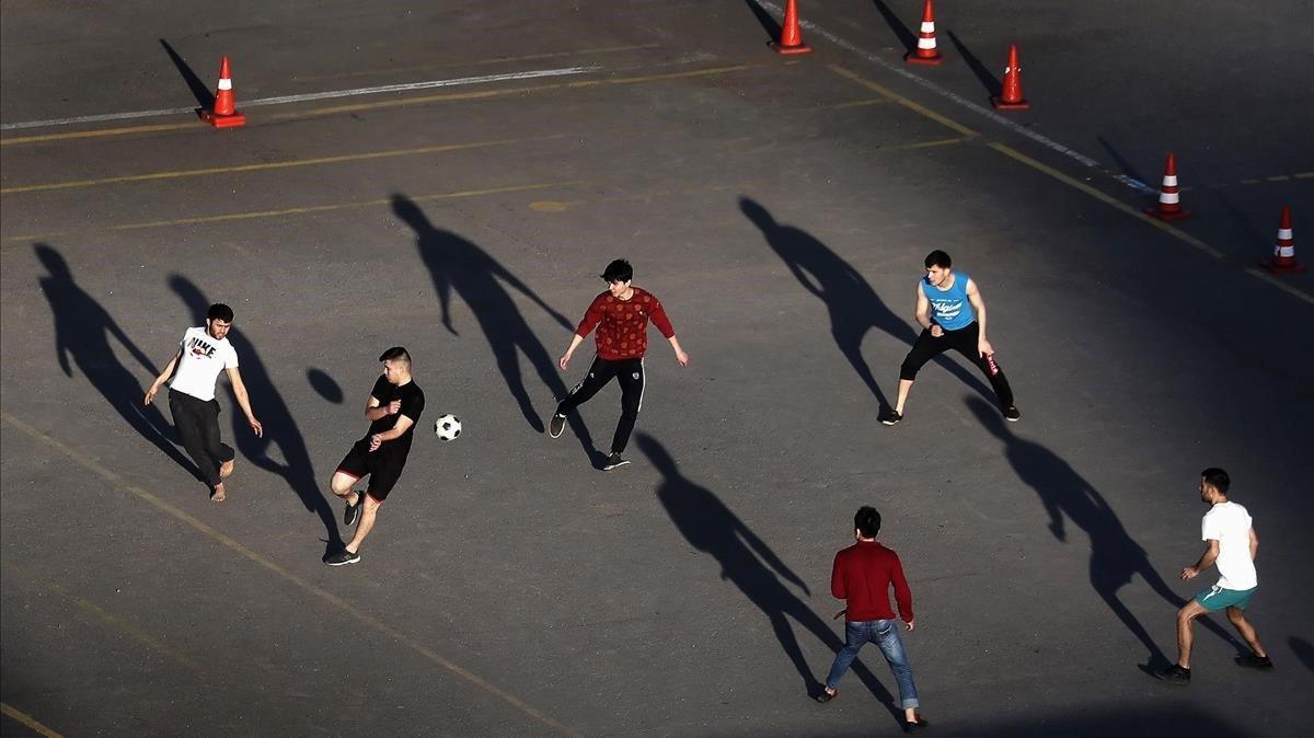 Varios jóvenes juegan a fútbol en una escuela de conducción cerrada al público