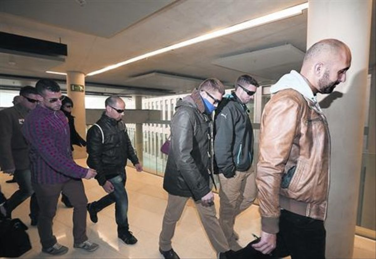 Un grupo de mossos acompañan a uno de los imputados, en la Ciutat de la Justícia.