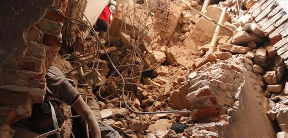 Un cadáver de una víctima, entre los escombros del edificio siniestrado.