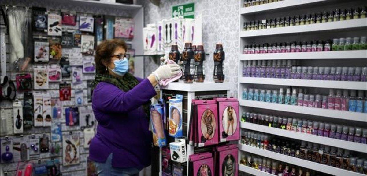 Una empleada de un 'sex shop' desinfecta productos en un establecimiento erótico.