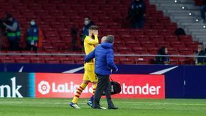 Piqué abandona lesionado el Metropolitano junto a Lluís Til, el médico del Barça.