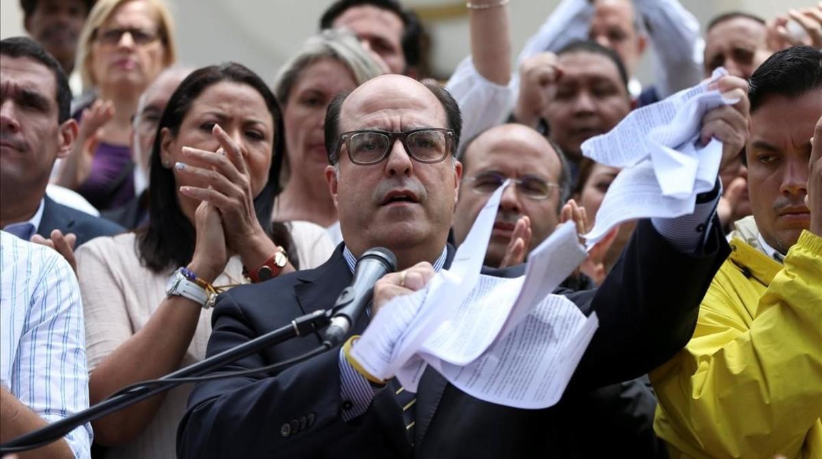 Julio Borges, presidente de la Asamblea nacional, rompe una copia de la sentencia del Supremo, en una rueda de prensa en Caracas, el 30 de marzo.