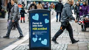 Una calle peatonal de Uppsala (Suecia) con un cartel en el que pone:'El peligro no ha terminado-Mantenga ladistancia'.