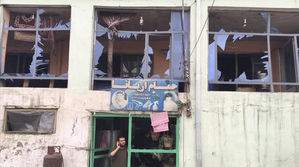 Un hombre habla por su teléfono móvil desde la entrada a su tienda dañada por un atentado cerca del Ministerio de Defensa en Kabul,Afganistán.