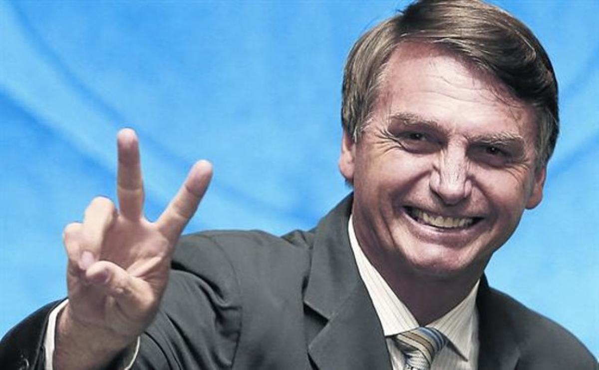 El polémico Jair Bolsonaro saluda sonriente durante un pleno del Senado brasileño, el pasado febrero, en Brasilia.