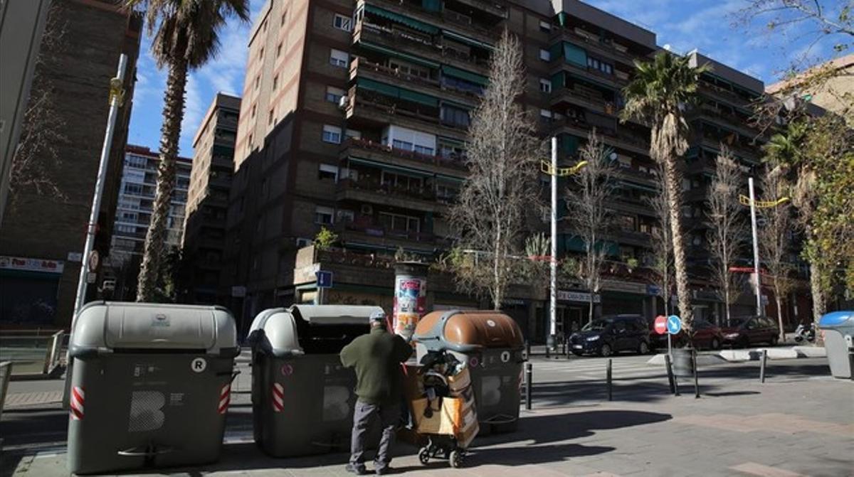Un hombre escarba en un contenedor en la calle de Marne, en Nou Barris.
