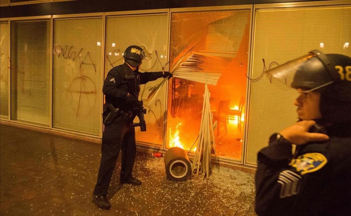 La policía investiga un incendio provocado por los manifestantes durante una protesta anti-Trump en Oakland, California.