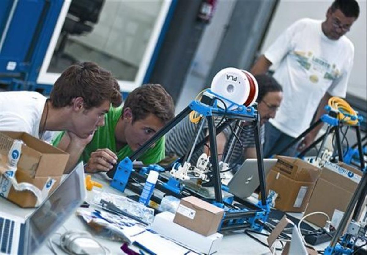Prototipos 8 Tres participantes en el taller de Les Corts observan la impresión de las máquinas, el viernes.