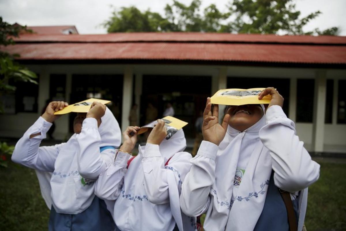 Un grupo de estudiantes prueban unos filtros para observar el eclipse de sol, este lunes en la isla indonesia de Ternate.