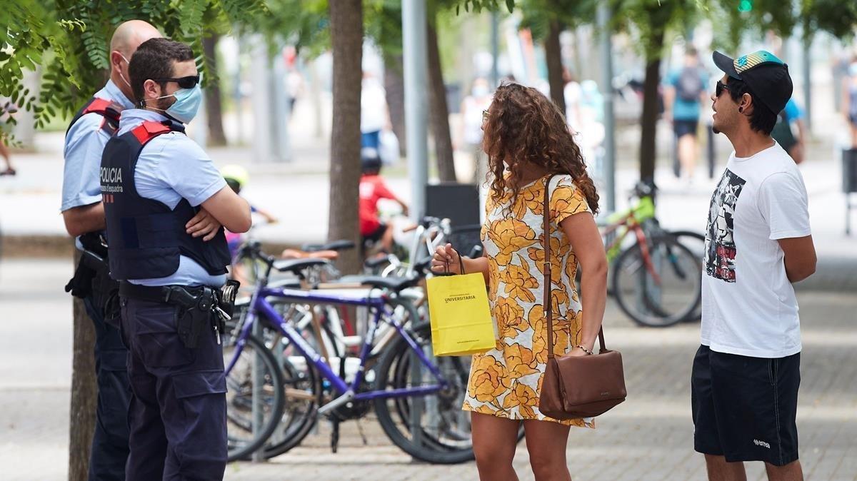 Unos agentes de los Mossos d Esquadra informan a una pareja del uso obligatorio de la mascarilla, en julio pasado en Barcelona.