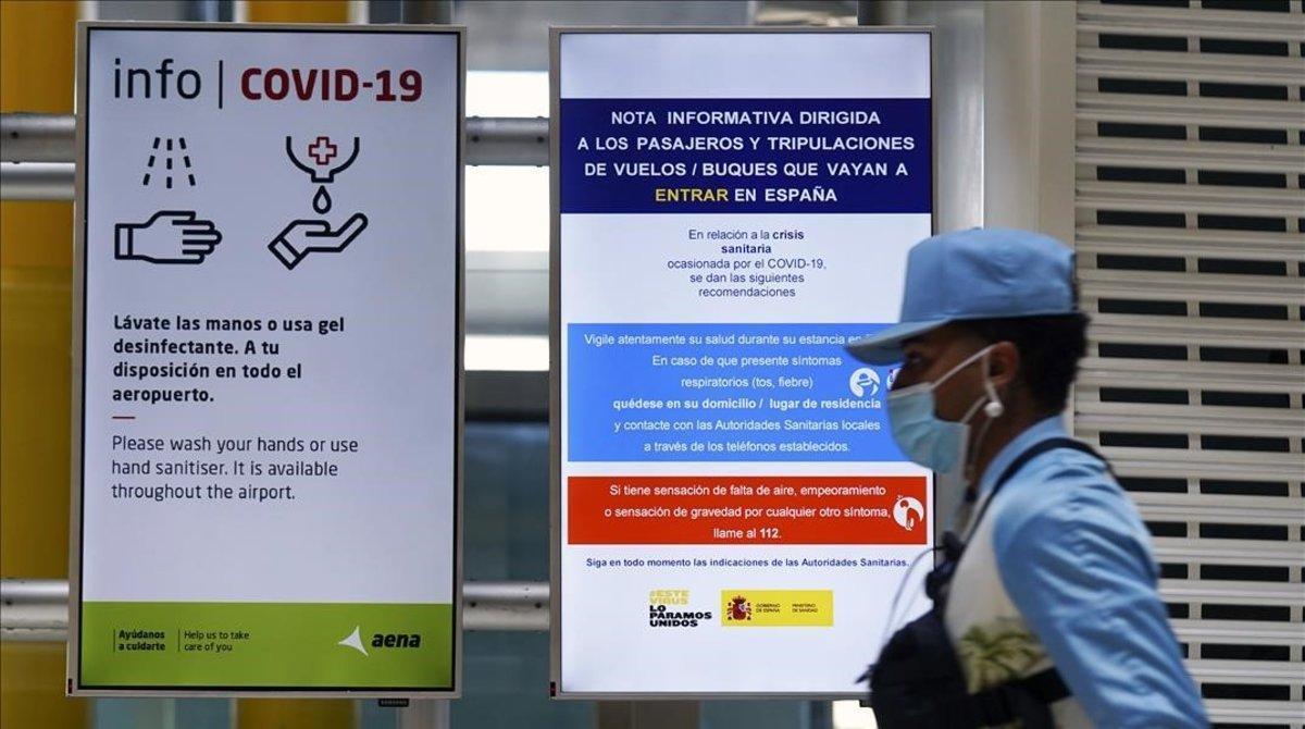 Una mujer camina por los pasillos del aeropuerto de Madrid, protegida con mascarilla, el primer día laborable tras la finalización del estado de alarma.