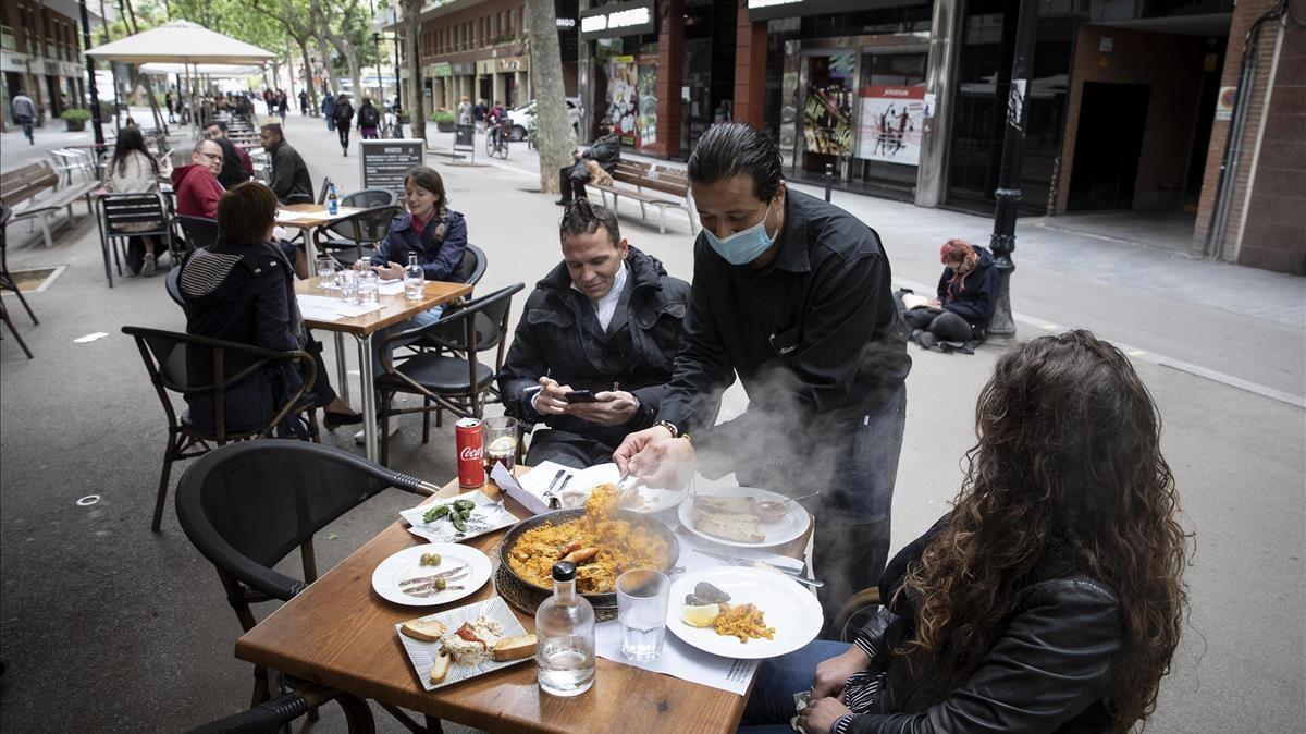 Un camanero sirve una paella en la terraza de un restaurante de la Rambla del Poblenou este pasado mes de abril.