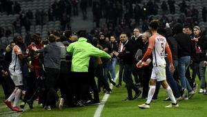 Los aficionados ultras del Lille invaden el terreno de juego tras el empate contra el Montpellier (1-1).