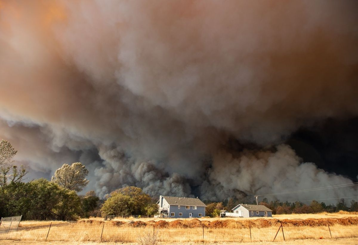 A home is overshadowed by towering smoke plumes as the Camp fire races through town in ParadiseCalifornia- With the embers still raining from blackened skies choked by California s massive wildfiresthe effort turns to rebuilding ParadisePhoto by Josh EdelsonAFP