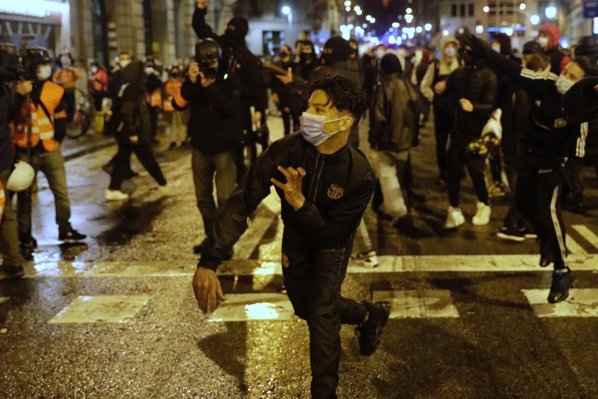 Manifestantes lanzando piedras en Via Laietana, en Barcelona, en el séptimo día de movilizaciones por Hasél.