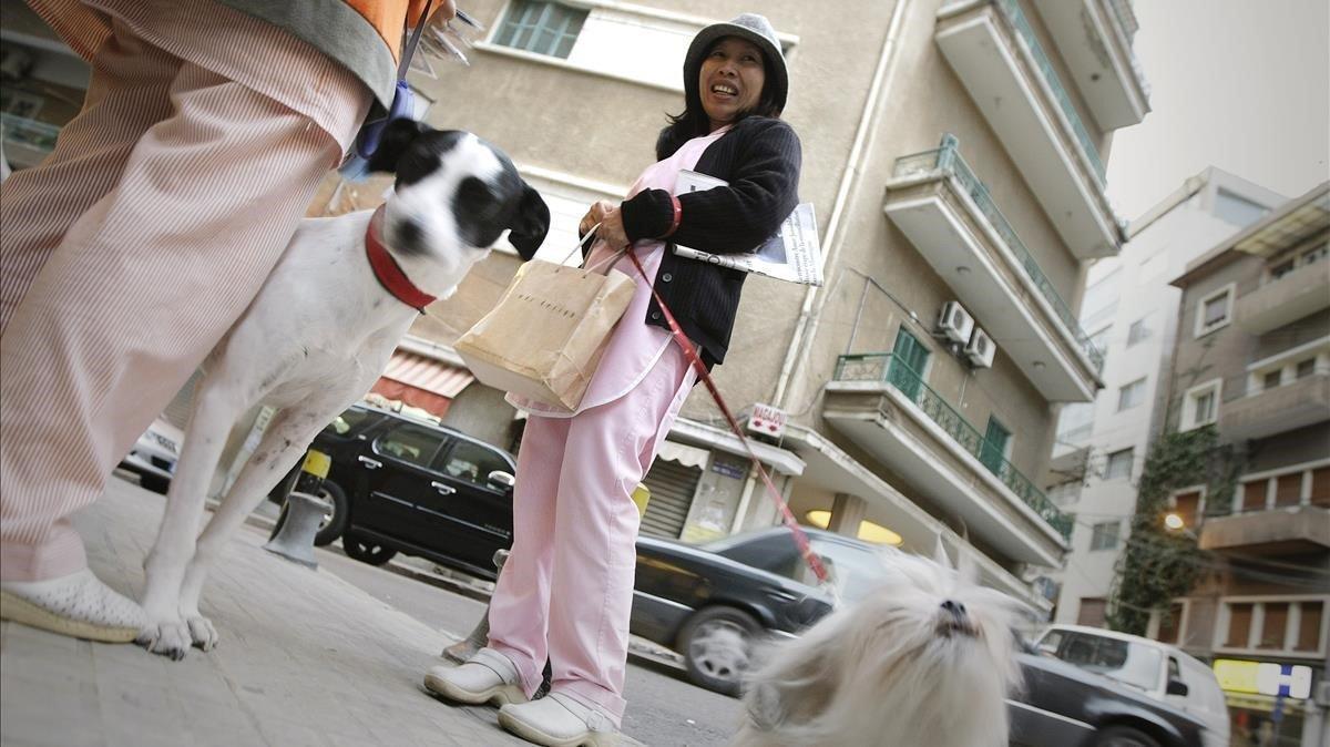 Una empleada doméstica filipina pasea un perro en Beirut.